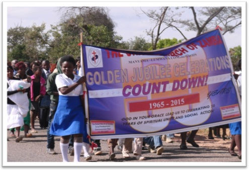 The group grew bigger and thicker as it approached the church building Marching to the New Church Building at Manyama.